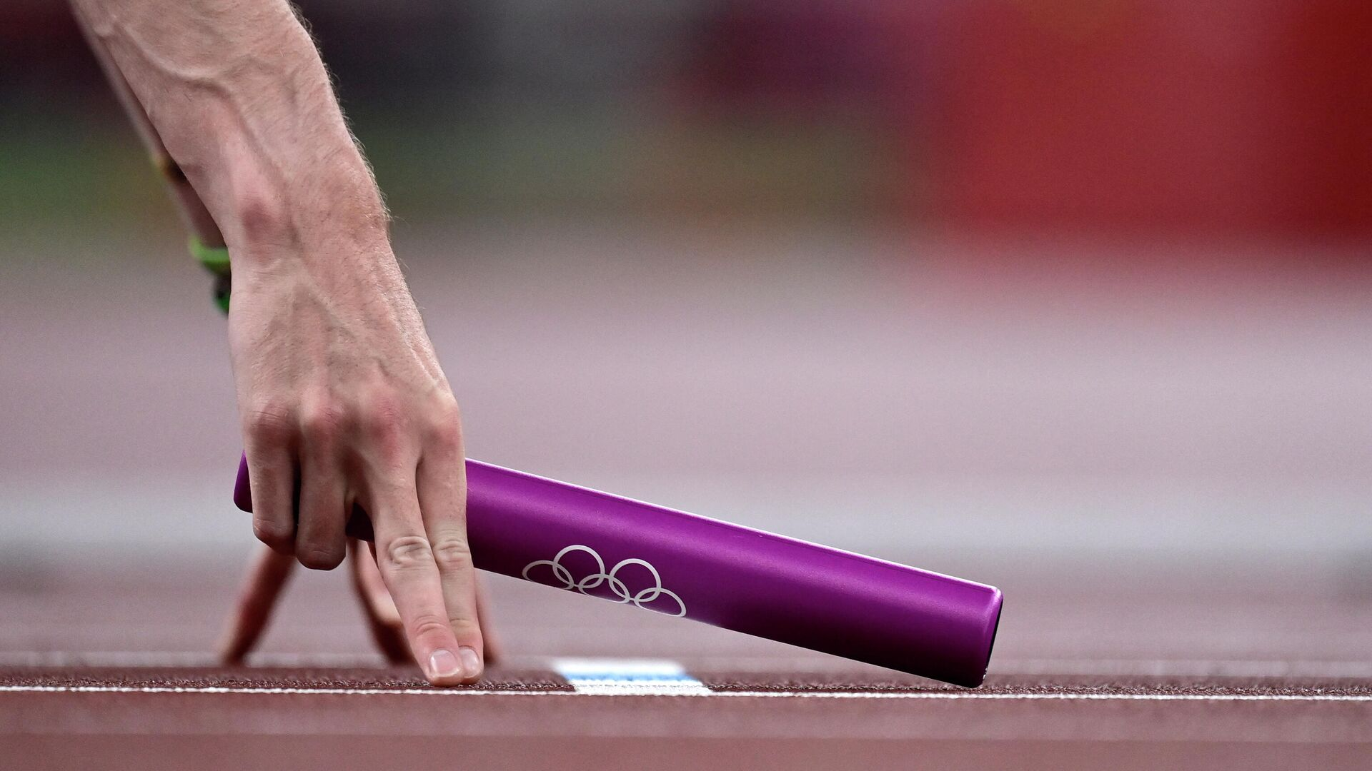 An athlete holds a relay baton ahead of the mixed 4x400m relay heats during the Tokyo 2020 Olympic Games at the Olympic Stadium in Tokyo on July 30, 2021. (Photo by Javier SORIANO / AFP) - РИА Новости, 1920, 30.07.2021