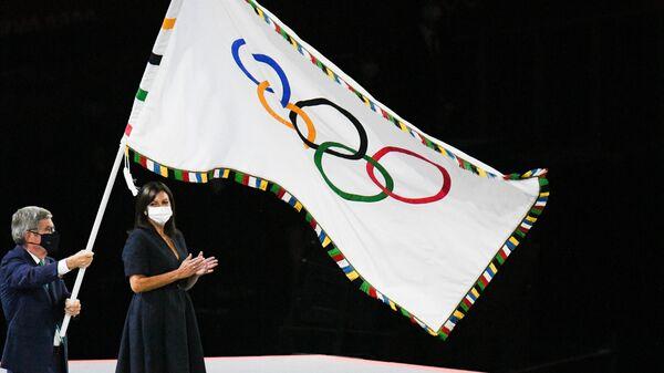 Президент Международного олимпийского комитета (МОК) Томас Бах и мэр Парижа Анн Идальго на торжественной церемонии закрытия XXXII летних Олимпийских игр в Токио на Национальном олимпийском стадионе