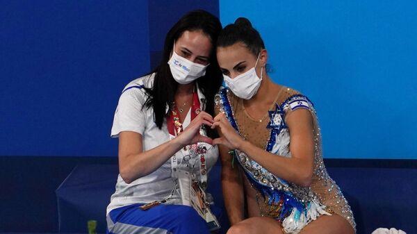 Линой Ашрам (Израиль) с тренером после выполнения упражнения с лентой на Олимпийских играх в Токио