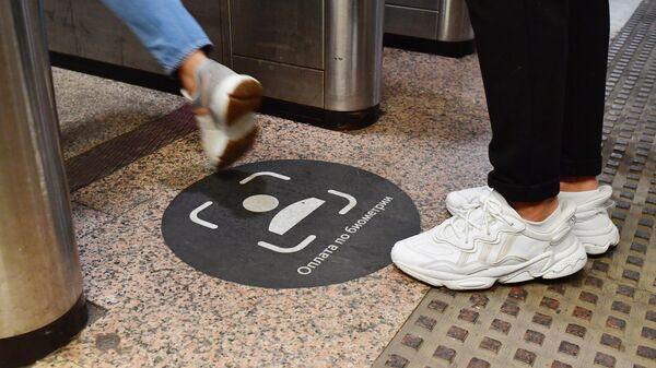 Пассажиры проходят через турникет с новой системой Face Pay для оплаты проезда по лицу на Филевской линии Московского метрополитена
