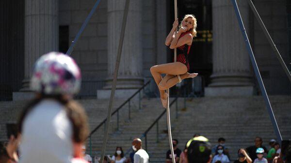 Акробат выступает на мероприятии Summer street в Нью-Йорке