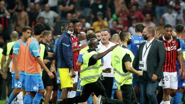Футболисты и сотрудники стадиона во время матча Ницца - Марсель