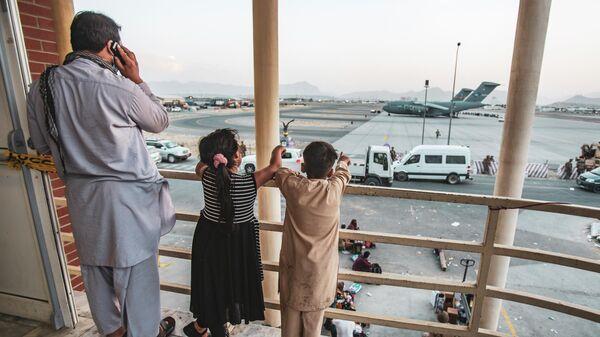 Афганская семья во время эвакуации в аэропорту Кабула