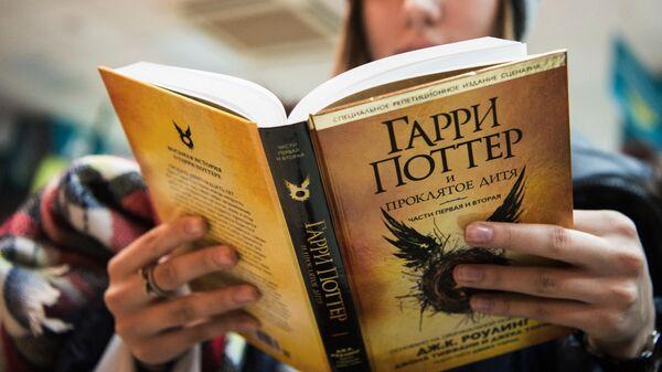 Покупательница с книгой Джоан Роулинг Гарри Поттер и проклятое дитя