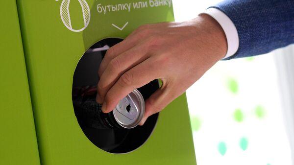 Мужчина сдает алюминиевую банку в фандомат по сбору пластиковой и алюминиевой тары, для дальнейшей переработки