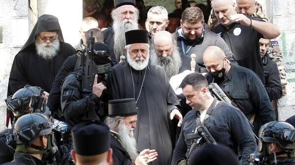 Сотрудники службы безопасности сопровождают Патриарха Портфирия и епископа Иоаникия у монастыря в Цетине, Черногория