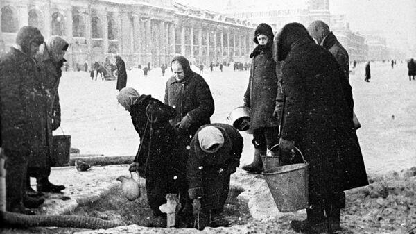 Жители блокадного Ленинграда набирают воду, появившуюся после артобстрела в пробоинах в асфальте на Невском проспекте