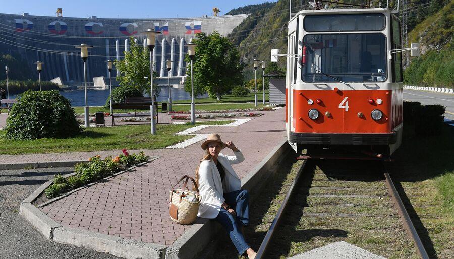 Девушка позирует возле трамвая у плотины Саяно-Шушенской ГЭС на реке Енисей