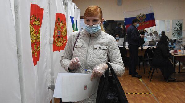 Женщина во время голосования на выборах в Госдуму во Владивостоке