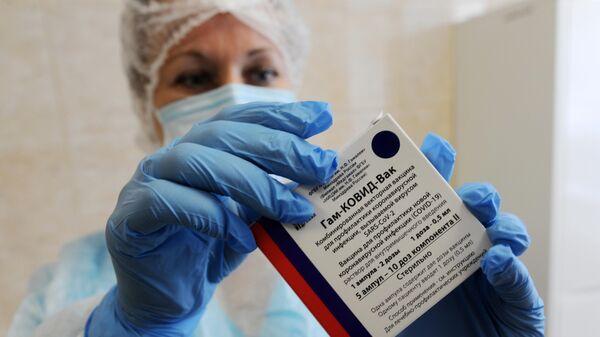Медицинская сестра держит в руках коробку с вакциной Гам-Ковид-Вак (Спутник V)