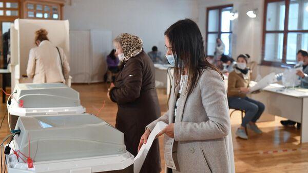 Избиратели во время голосования на выборах депутатов Государственной Думы на избирательном участке № 60 в Москве