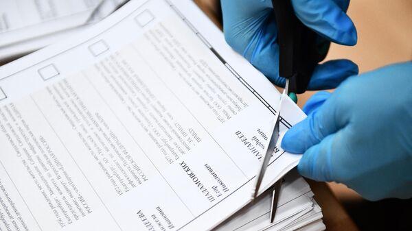 Процедура погашения неиспользованных избирательных бюллетеней после закрытия избирательного участка в Екатеринбурге на выборах депутатов Государственной Думы РФ