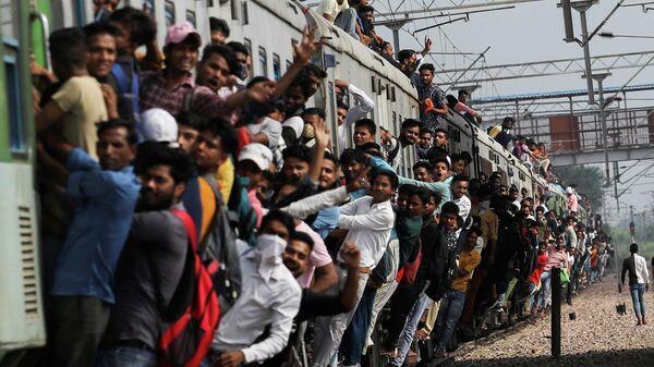 Люди цепляются за переполненный поезд, когда он покидает вокзал во время продолжающейся вспышки коронавирусной болезни (COVID-19) в Газиабаде, Индия