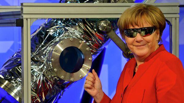 Канцлер Германии Ангела Меркель в защитных очках в школьной лаборатории DLR во время посещения Европейского центра астронавтов ESA