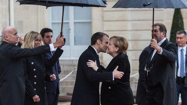 Президент Франции Эммануэль Макрон приветствует канцлера ФРГ Ангелу Меркель у Елисейского дворца перед началом мероприятий, посвященных 100-летию окончания Первой мировой войны