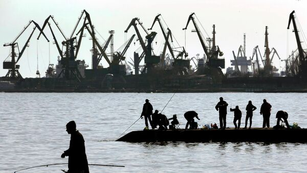 Люди ловят рыбу на пирсе в порту Мариуполя