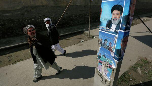 Мужчины смотрят на плакат кандидата в президенты Афганистана