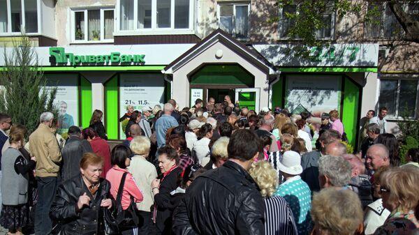 Вкладчики стоят в очереди у центрального отделения ПриватБанка в Симферополе. Архивное фото