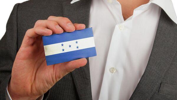 Мужчина держит карточку с флагом Гондураса. Архивное фото