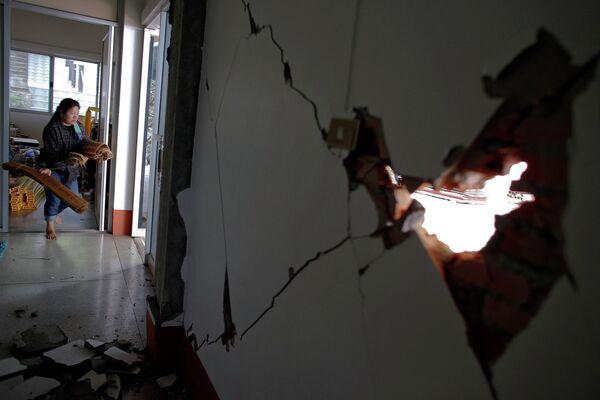 Женщина выносит вещи из дома, поврежденного в результате землетрясения в Таиланде