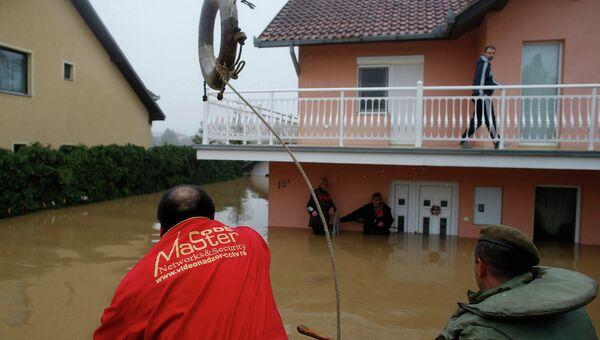 Человек бросает спасательный круг в сторону людей, которые ждут эвакуации из затопленном доме в городе Оберновац