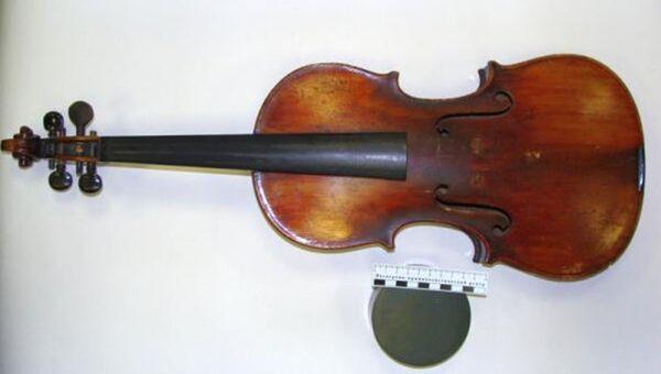 Антикварный музыкальный инструмент в черном футляре: скрипка без струн, на внутренней поверхности которой имеется надпись, выполненная латинскими буквами на небольшом фрагменте бумаги: Antonius Stradiuarius Cremonensis Faciebat Anno 1721