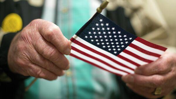 Американский ветеран Второй мировой войны держит флаг США