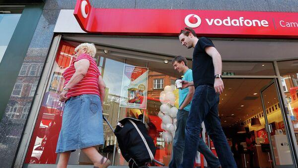 Жители проходит мимо магазина Vodafone в Лондоне
