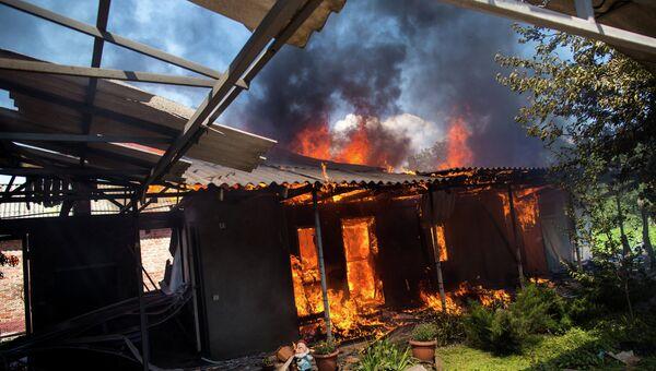 Горящие дома после массированного артиллерийского обстрела поселка Черевковка под Славянском. Архивное фото