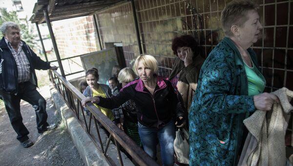 Жители поселка Николаевка выходят из подвала, где они укрывались во время обстрела