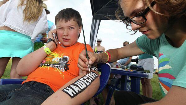 Мастер наносит ребенку на руку логотип рок-фестиваля Нашествие