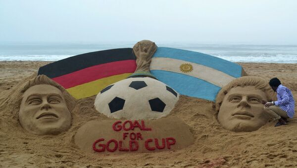 Песчаная скульптура на пляже в Индии, изображающая Кубок мира, а также капитана сборной Германии Филиппа Лама и капитана сборной  Аргентины Лионеля Месси