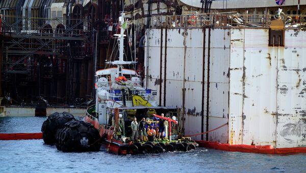 Рабочие начинают работы по подготовке к перемещению в порт Генуи пассажирского лайнера Коста Конкордия. Архивное фото