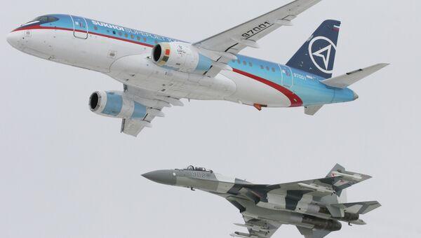 Самолет Sukhoi SuperJet-100 (вверху) в сопровождении истребителя Су-35 (внизу). Архивное фото