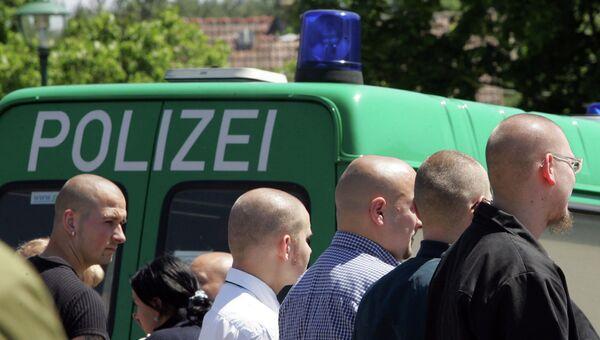 Немецкие неонацисты возле полицейской машины в Германии