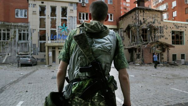 Боец ополчения на подвергшейся обстрелу украинской армией улице Донецка. Архивное фото