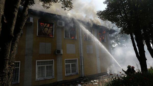 Украинские пожарные потушат огонь в разрушенном здании