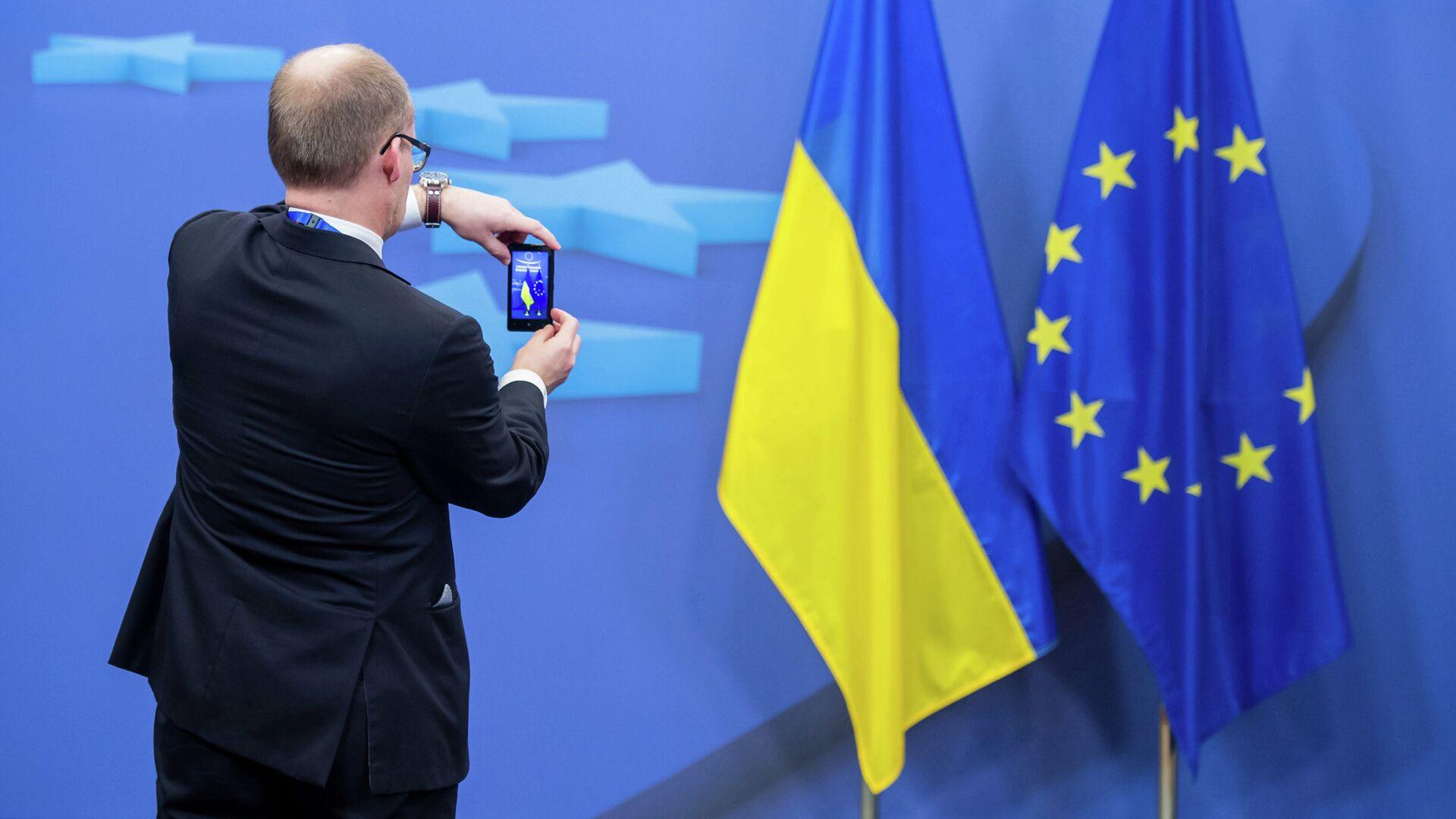 Человек фотографирует флаги Украины и Евросоюза - РИА Новости, 1920, 11.09.2021