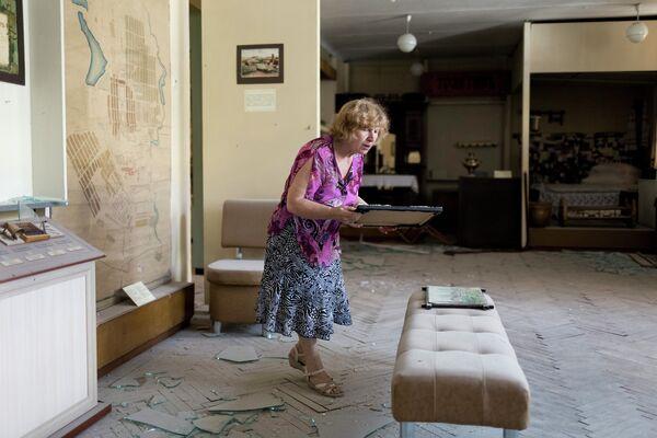 Сотрудница музея в Донецке убирается в выставочном зале после обстрела