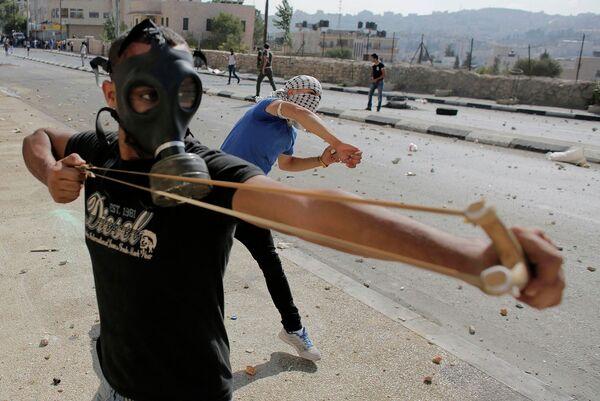Палестинский демонстрант использует рогатку во время столкновений с Израильскими военными в секторе Газа