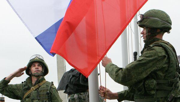 Солдаты поднимают российский флаг в полевом лагере. Архивное фото