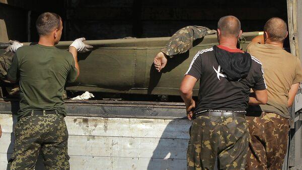 Украинские военные грузят в грузовик тела погибших товарищей
