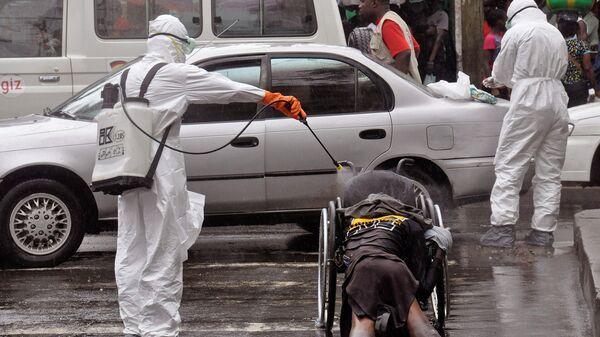 Медицинские работники обрызгивают тело, подозреваемого в смерти от вируса Эбола