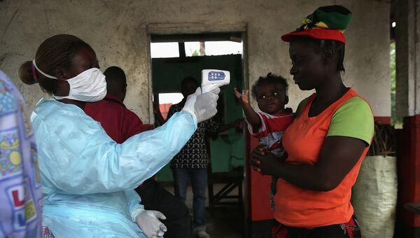 Врач проверяет население на симптомы лихорадки Эбола, Либерия. Архивное фото