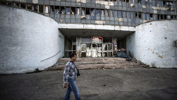 Житель Луганска проходит мимо здания, поврежденного артобстрелом. Архивное фото.