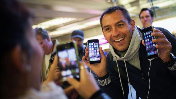 Мужчина с телефонами iPhone 6 и iPhone 6 Plus в первый день продаж в магазине Apple в Нью-Йорке