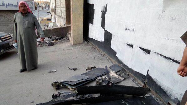 Житель города Раккаа осматривает упавший беспилотник армии США