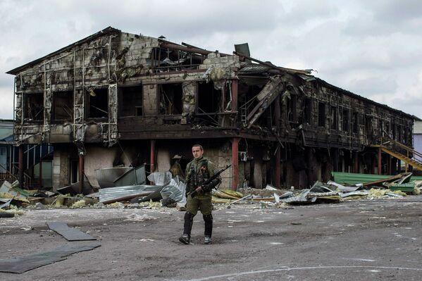 Боец народного ополчения возле разрушенного завода в селе Нижняя Крынка