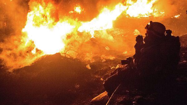 Курильщик возле горящих покрышек в Киеве. Архивное фото