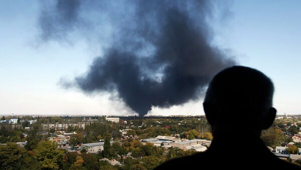 Житель города смотрит на дым над Донецком. Архивное фото